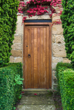 Solid wood Door at the end of a ston path wieth a yew hedge Stock Photo
