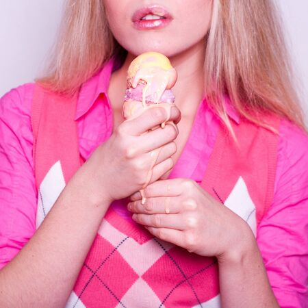 melting ice cream held by blonde girl in pink shirt  Stock Photo