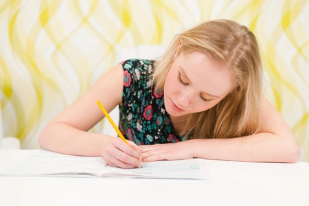 Beautiful young woman writing an exam and studying  Stock Photo