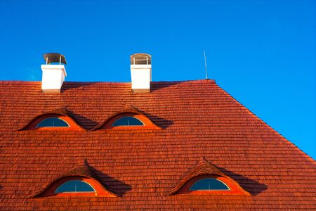 red roof with baroque windows on blue sky background