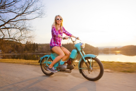 girl in shorts: Young beautiful woman riding a lifestyle vintage bike during sunset