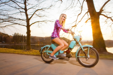 Young beautiful woman riding a lifestyle vintage bike during sunset