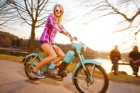 Young beautiful woman riding a lifestyle vintage bike during sunset photo