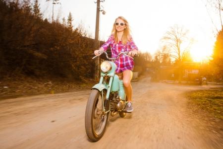 motorrad frau: Junge schöne Frau auf einem Fahrrad Lifestyle-Jahrgang während des Sonnenuntergangs Lizenzfreie Bilder