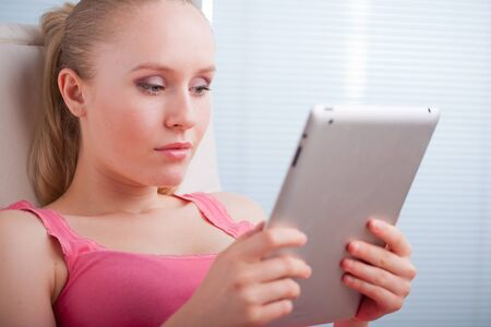 Young beautiful student using a tablet computer while relaxing photo