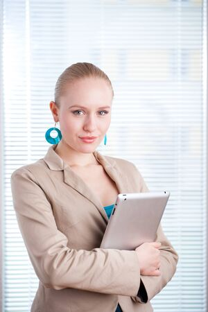 easy chair: beautiful young positive business woman-student using a tablet on clean background  lots of copyspace
