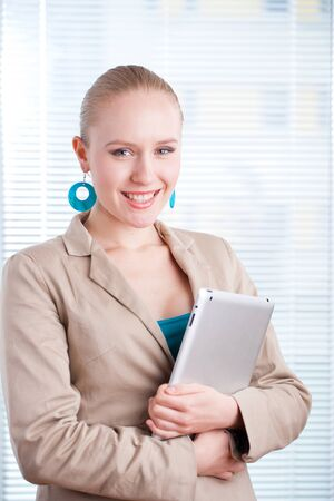 beautiful young positive business woman-student using a tablet on clean background  lots of copyspace photo