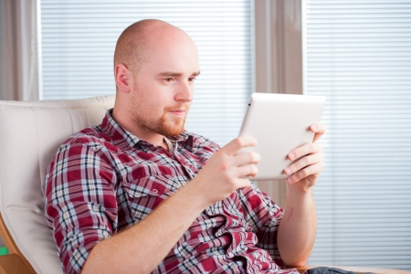 Focused man working and playing with tablet computer  lots of copyspace