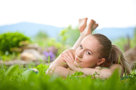 portrait of young beautiful positive woman lying and relaxing in the fresh spring grass with colorful garden behind Standard-Bild