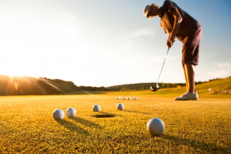 tee off: Male golf player practicing a par during beautiful evening sunshine light Stock Photo