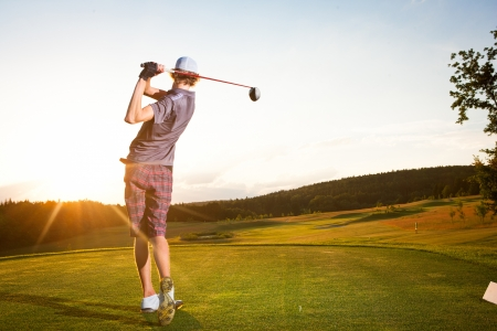 Male golf player teeing off golf ball from tee box to beautiful sunset Stock Photo