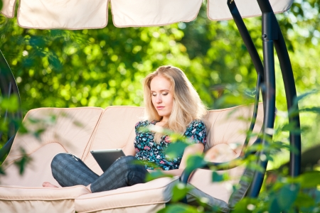 Positive beautiful young woman sitting outdoors in armchair seat with tablet computer with fresh green background