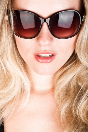 shades: studio closeup portrait of a young beautiful woman in vintage sunglasses