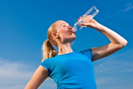 young female athlete drinkig water to refresh during a hot weather running, blue sky background