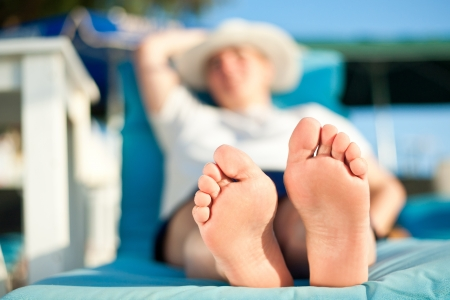 mature woman feet relaxing on the beach during tropical vacation