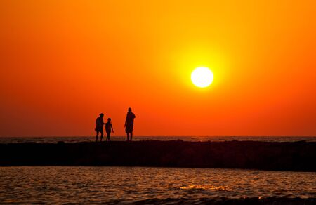 Silhouette of happy family enjoying while walking on the beach at beautiful sunset photo