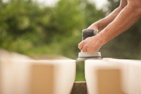 Closeup of a handyman  carpenter s hand sanding a wood with sander photo