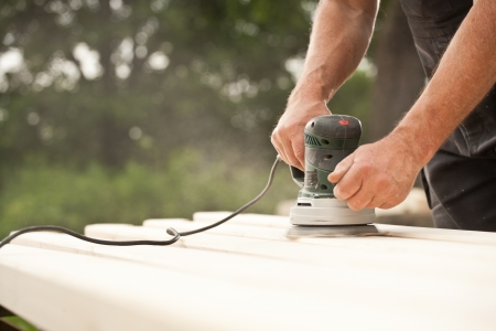 Closeup of a handyman  carpenter s hand sanding a wood with sander Stock Photo - 14618299