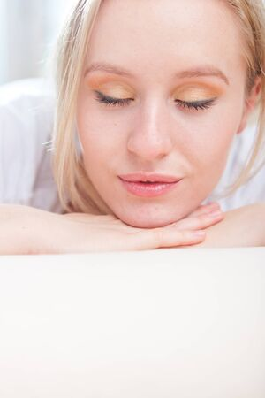 Closeup portrait of happy attractive young woman resting her head on her hand while relaxing on the floor Stock Photo - 14649427
