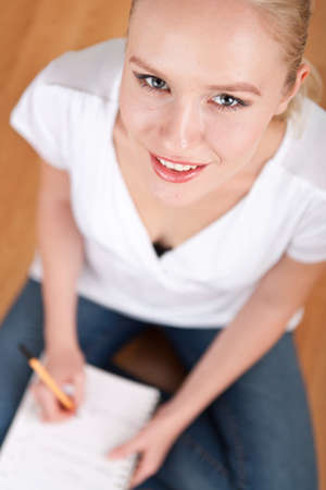 Beautiful young female student taking notes while studying and smiling into the camera Stock Photo - 14750620