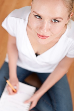 Beautiful young female student taking notes while studying and smiling into the camera Stock Photo - 14750593