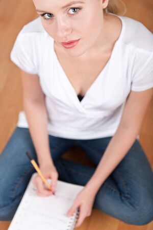 Beautiful young female student taking notes while studying and smiling into the camera Stock Photo - 14750600