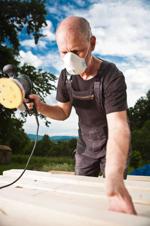 Carpenter sanding a wood with sander with dramatic dark sky background Stock Photo - 14750636