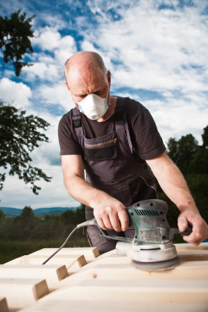 Carpenter sanding a wood with sander with dramatic dark sky background Stock Photo