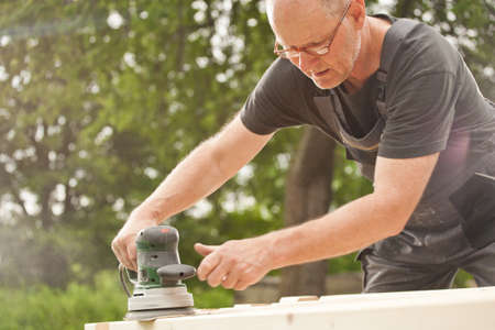 Carpenter sanding a wood with sander, outdoors Stock Photo - 14750665