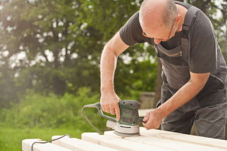 Carpenter sanding a wood with sander, outdoors Stock Photo - 14750667