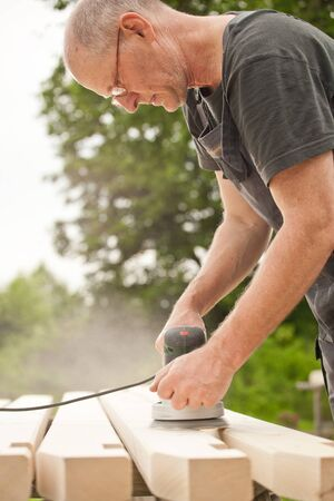 Carpenter sanding a wood with sander, outdoors Stock Photo - 14750643