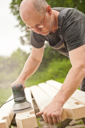 Carpenter sanding a wood with sander, outdoors