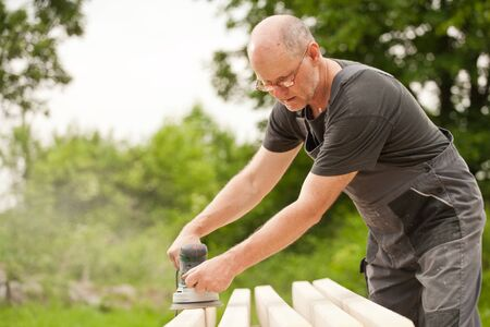 Carpenter sanding a wood with sander, outdoors Stock Photo - 14750641