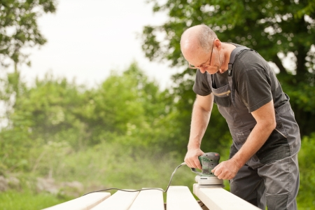 Carpenter sanding a wood with sander, outdoors Stock Photo - 14750635