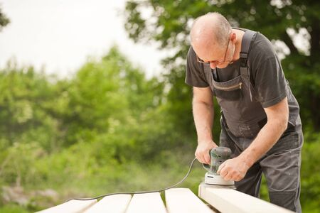 Carpenter sanding a wood with sander, outdoors photo