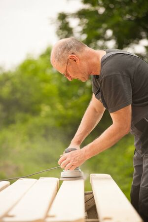 Carpenter sanding a wood with sander, outdoors Stock Photo - 14750638