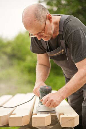 Carpenter sanding a wood with sander, outdoors Stock Photo - 14750662