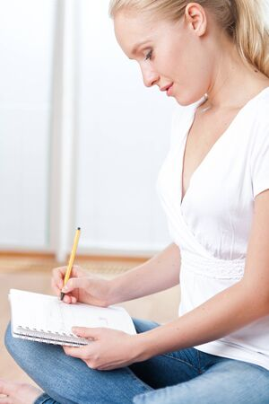 Closeup of young female student sitting on the floor and taking notes, studying and organizing Stock Photo - 14750623