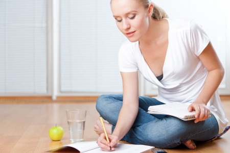Closeup of young female student sitting on the floor and taking notes, studying and organizing with healthy snack including apple and fresh water Stock Photo - 14750627