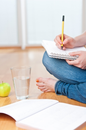 Closeup of young female student sitting on the floor and taking notes, studying and organizing with healthy snack including apple and fresh water
