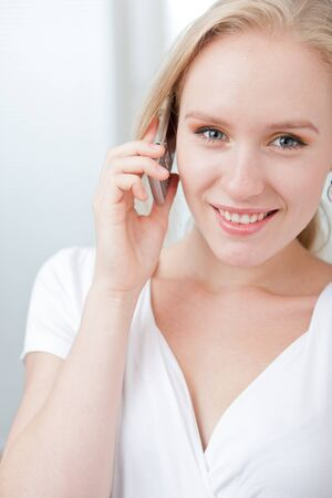 Closeup portrait of a happy young blond woman speaking on a cellphone photo