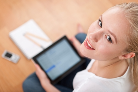 Young beautiful female female student using a tablet computer while studying and organizing her time  overshoulder, focused on head Stock Photo - 14750621