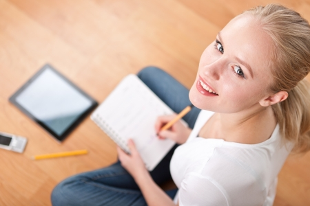 Young beautiful female female student using a tablet computer while studying and organizing her time  overshoulder, focused on head