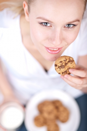 Cute young woman eating cookies and drinking milk, picture from above, model is smiling into the camera Standard-Bild