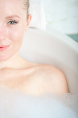Bath woman enjoying bathub  Naturally beautiful female relaxing in bath with foam in bathroom Stock Photo