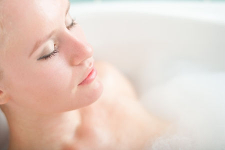 Bath woman enjoying bathub  Naturally beautiful female relaxing in bath with foam in bathroom Stock Photo