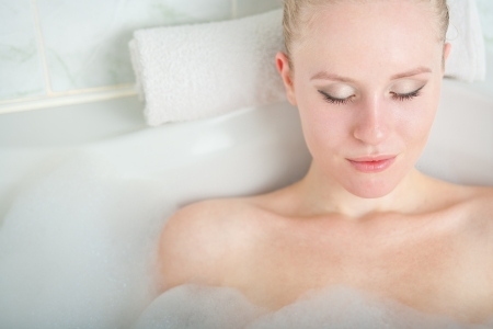 Bath woman enjoying bathub  Naturally beautiful female relaxing in bath with foam in bathroom photo