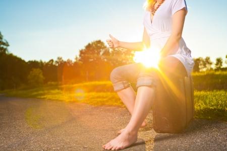 femme valise: Jolie jeune femme auto-stop le long d'une route de campagne au coucher du soleil, image ambiance vintage avec le coucher du soleil lens flare