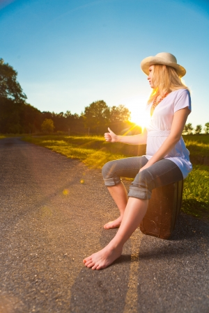 Pretty young woman hitchhiking along a countryside road during sunset, vintage mood picture with sunset lens flare