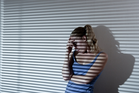 Portrait of a unhappy and depressed young woman in depressive stripe environment, desaturated image Stock Photo